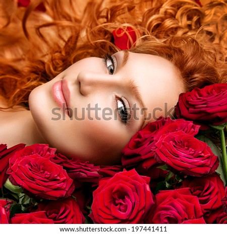 Beauty model girl with long curly red hair and beautiful red roses bouquet. Hairstyle with flowers. Fashion woman with Wavy healthy hair lying on beautiful roses. Permed hair - stock photo