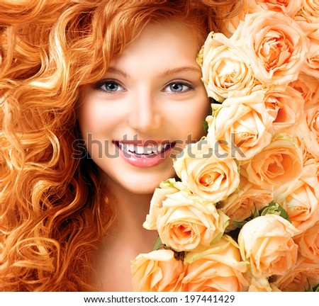 Beauty model girl with long curly red hair and beautiful red roses hairstyle. Fashion woman with Wavy healthy hair. Cute smiling teenage girl. Permed hair - stock photo