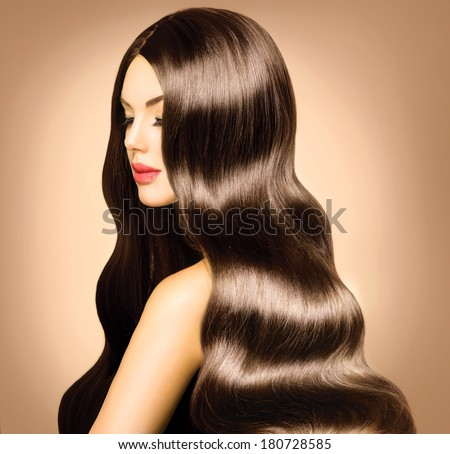 Beauty Model Girl with Long Healthy Wavy Hair and Perfect Makeup. Beautiful Woman with Shiny Brown Hair. - stock photo