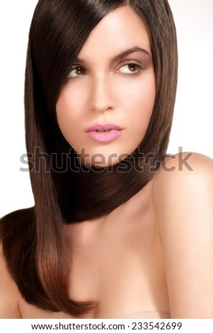 Beauty model showing perfect skin and long healthy brown hair on white