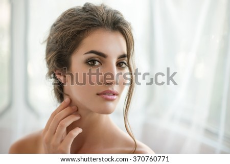 Beauty model with  make up and fresh skin is posing front of the window. Youth and Skin Care Concept.  Make up and Hair.  Close up, selected focus. - stock photo