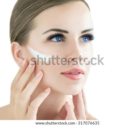 Beauty Model with  Perfect Fresh Skin and Long Eyelashes applying face cream. Youth and Skin Care Concept. Spa and Wellness. Make up and Hair. Lashes. Close up, selected focus. - stock photo
