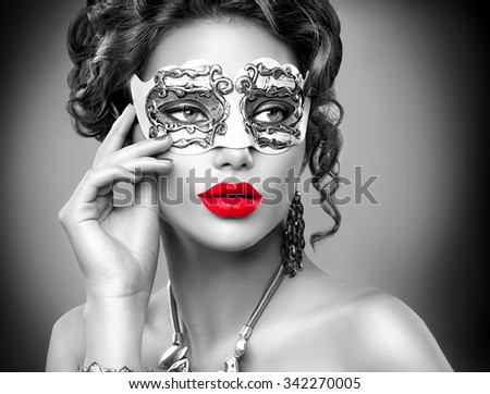 Beauty model woman wearing venetian masquerade carnival mask at party. Christmas and New Year celebration. Sexy girl with holiday makeup.Black and white portrait with Red lips - stock photo
