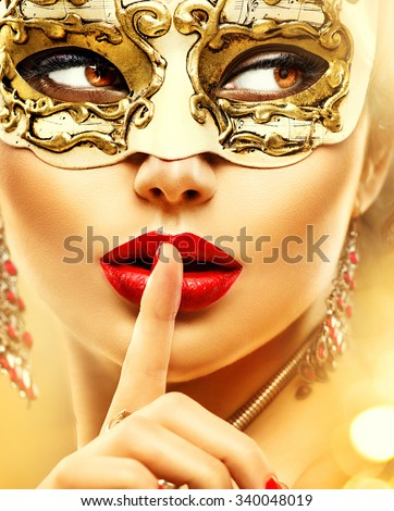 Beauty model woman wearing venetian masquerade carnival mask at party over holiday glowing gold background. Christmas and New Year celebration. Glamour lady with perfect make up and jewellery