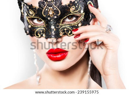 Beauty model woman wearing venetian masquerade carnival mask at party, over white background. Christmas and New Year celebration. Sexy girl with holiday makeup and manicure. Red lips and nails  - stock photo