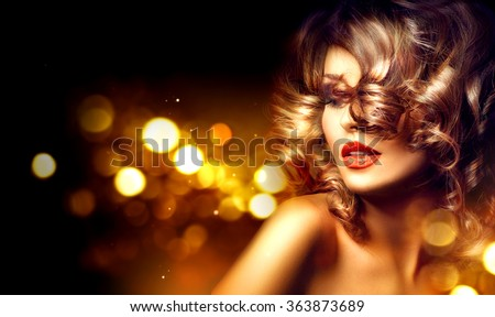 Beauty model woman with beautiful make up and curly hair style over holiday dark background with magic glow. Holiday celebration. Brunette Glamour lady with perfect make up and hairstyle - stock photo