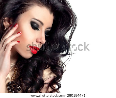 Beauty Model Woman with Long Black Curly Hair. Healthy Hair and Beautiful Professional Makeup. Red Sexy Lips and Smoky Eyes Make up with False Lashes. Gorgeous Glamour Lady Portrait. Red Manicure.  - stock photo