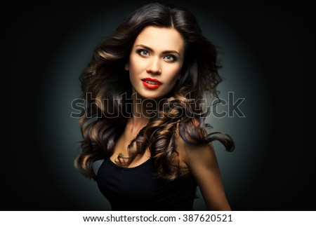 Beauty Model Woman with Long Brown Wavy Hair. Healthy Hair and Beautiful Professional Makeup. Red Lips and Smoky Eyes Make up. Gorgeous Glamour Lady Portrait. Haircare, Skincare concept