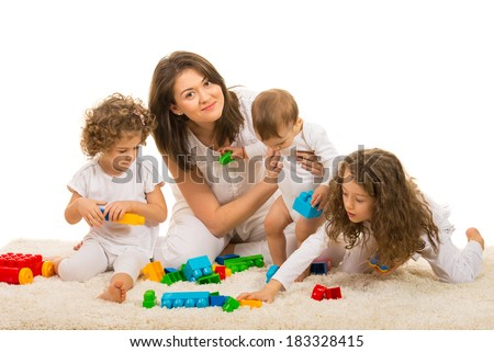 Beauty mom playing with her kids home and sitting together on fur carpet - stock photo
