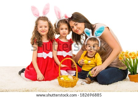 Beauty mother and  kids with bunny ears sitting on carpet with Easter basket - stock photo