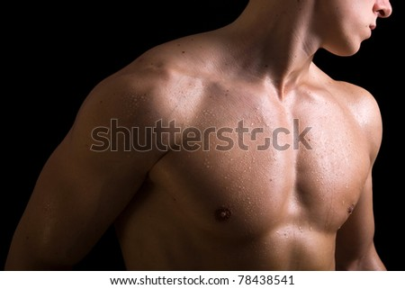 Beauty naked torso of young muscular man on black background - stock photo