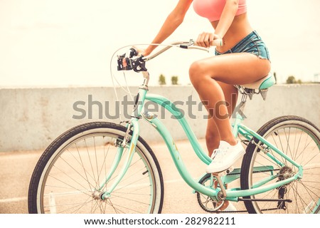 Beauty on bicycle. Close-up of beautiful young woman with perfect curves riding bicycle - stock photo
