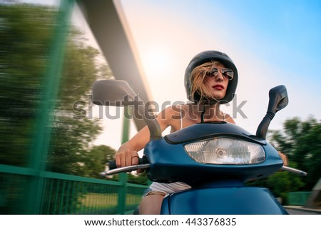 Beauty on scooter. Excited young and beautiful woman riding scooter along the street. - stock photo