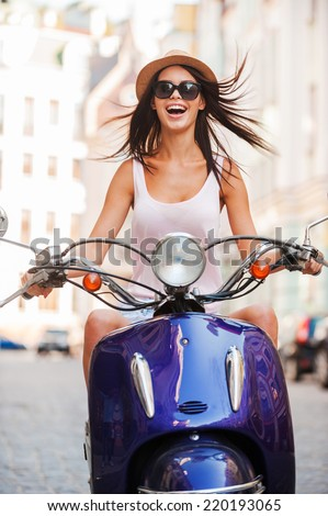 Beauty on scooter. Excited young and beautiful woman riding scooter along the street and keeping mouth open - stock photo