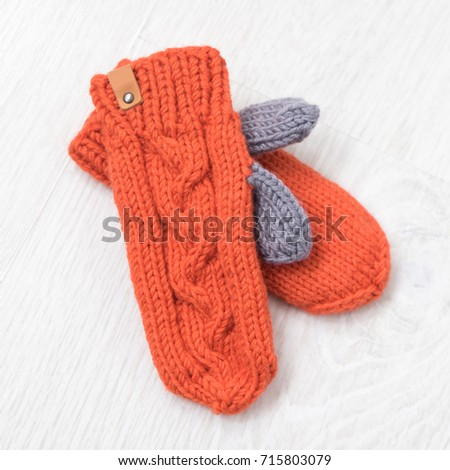 beauty orange knitted mittens on white background. flat lay, top view