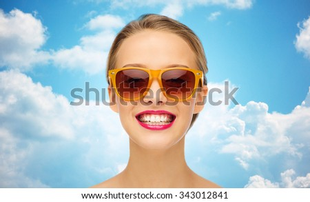 beauty, people, accessory and fashion concept - smiling young woman in sunglasses with pink lipstick on lips over blue sky and clouds background - stock photo