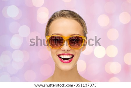 beauty, people, accessory and fashion concept - smiling young woman in sunglasses with pink lipstick on lips over pink holidays lights background - stock photo