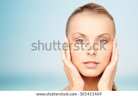 beauty, people and body care concept - beautiful young woman touching her face over blue background - stock photo