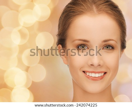beauty, people and health concept - beautiful young woman face over beige lights background - stock photo