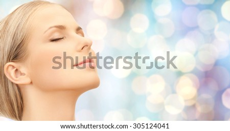 beauty, people and health concept - beautiful young woman face over blue holidays lights background - stock photo