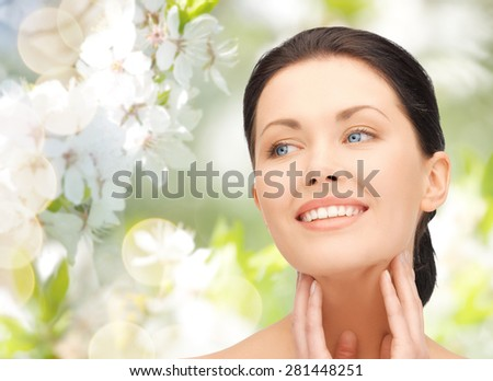 beauty, people and health concept - beautiful young woman touching her face and neck over green blooming garden background - stock photo