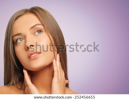 beauty, people and health concept - beautiful young woman touching her face and neck over violet background - stock photo