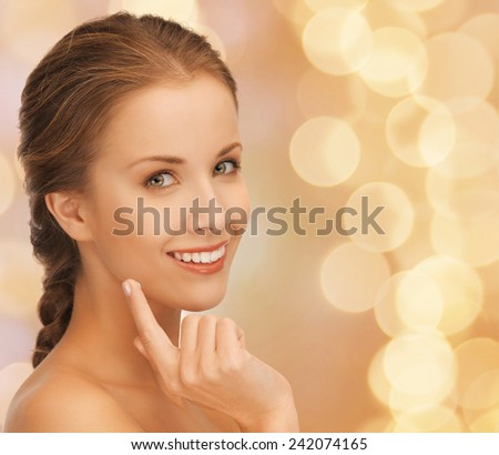 beauty, people and health concept - beautiful young woman touching her face over beige lights background - stock photo