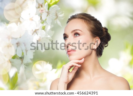 beauty, people and health concept - beautiful young woman touching her face over natural spring cherry blossom background - stock photo