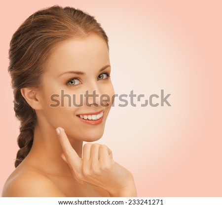 beauty, people and health concept - beautiful young woman touching her face over pink background - stock photo