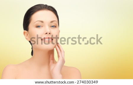 beauty, people and health concept - beautiful young woman touching her face over yellow background - stock photo