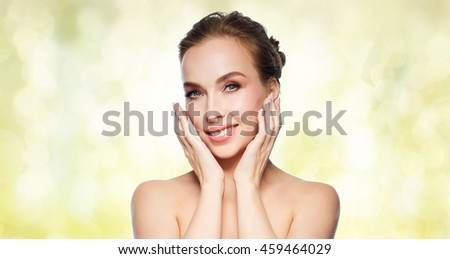 beauty, people and health concept - beautiful young woman touching her face over yellow holidays lights background - stock photo
