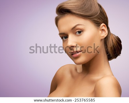 beauty, people and health concept - beautiful young woman with bare shoulders over violet background - stock photo