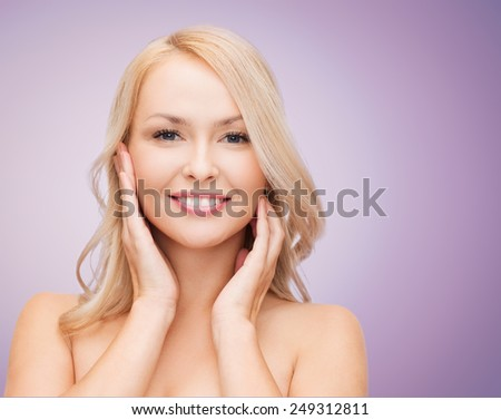 beauty, people and health concept - beautiful young woman with bare shoulders touching her face over violet background - stock photo