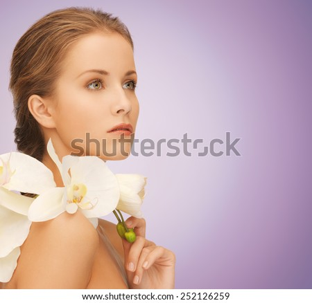 beauty, people and health concept - beautiful young woman with orchid flowers and bare shoulders over violet background - stock photo