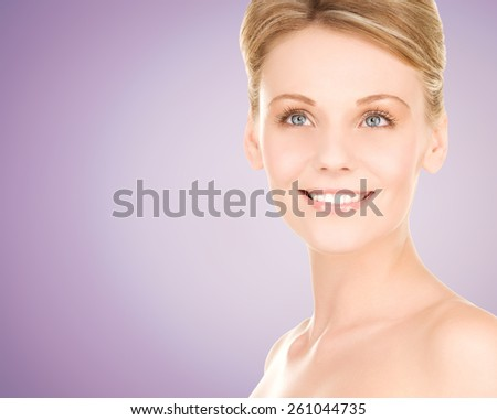 beauty, people and health concept - close up of beautiful young woman face over violet background - stock photo