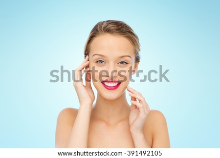 beauty, people and health concept - smiling young woman face with pink lipstick on lips and shoulders over blue background - stock photo