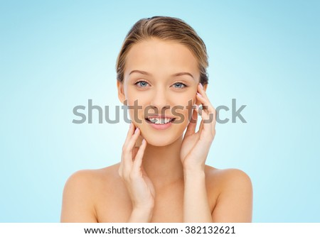 beauty, people and health concept - smiling young woman with bare shoulders touching her face over blue background - stock photo