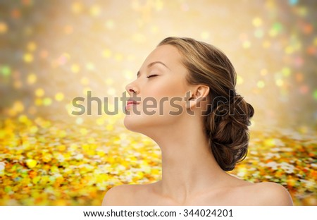 beauty, people and health concept - young woman face with closed eyes and shoulders side view over golden holidays lights or yellow glitter background - stock photo