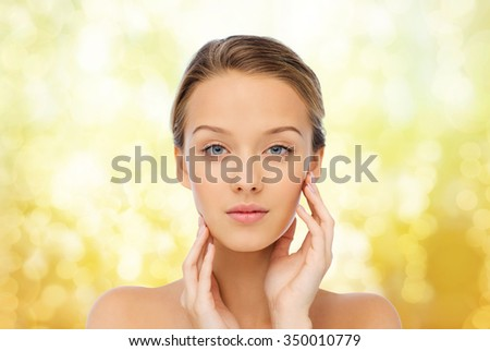 beauty, people and health concept - young woman with bare shoulders touching her face over yellow holidays lights background - stock photo