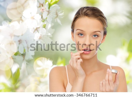 beauty, people and lip care concept - young woman applying lip balm to her lips over green natural background with cherry blossoms - stock photo
