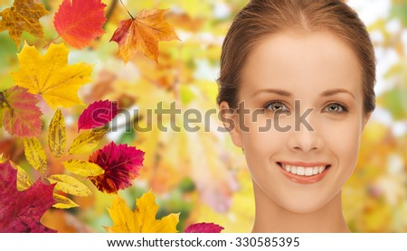 beauty, people and season concept - beautiful young woman face over autumn leaves background - stock photo