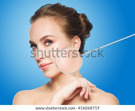 beauty, people and skin care concept - beautiful young woman face and circle with magnified smooth facial skin area over blue background - stock photo