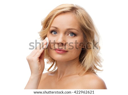 beauty, people and skincare concept - young woman cleaning face and removing make up with cotton pad - stock photo