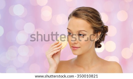 beauty, people and skincare concept - young woman cleaning face with exfoliating sponge over pink holidays lights background - stock photo