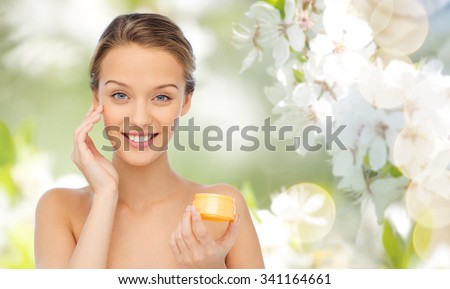 beauty, people, cosmetics, skincare and cosmetics concept - happy young woman applying cream to her face over summer green natural background with cherry blossom - stock photo