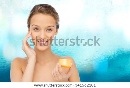 beauty, people, cosmetics, skincare and cosmetics concept - happy young woman applying cream to her face - stock photo