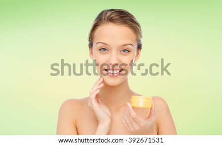 beauty, people, cosmetics, skincare and cosmetics concept - happy young woman applying cream to her face over green natural background - stock photo