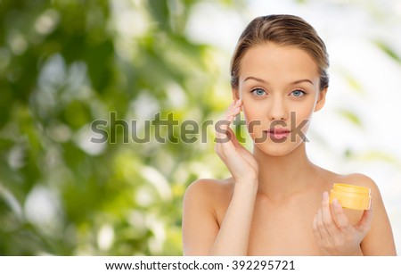 beauty, people, cosmetics, skincare and cosmetics concept - young woman applying cream to her face over green natural background - stock photo