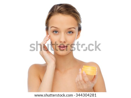 beauty, people, cosmetics, skincare and cosmetics concept - young woman appying cream to her face - stock photo