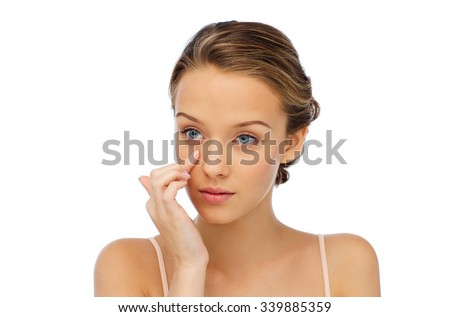 beauty, people, cosmetics, skincare and health concept - young woman applying cream to her face - stock photo